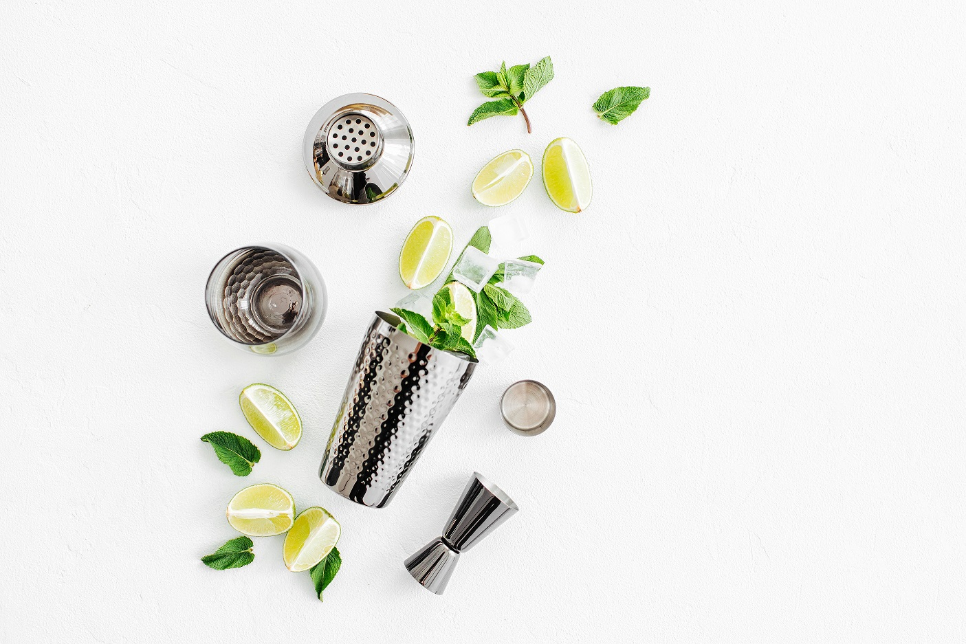cocktail shaker with mint leaves and limes